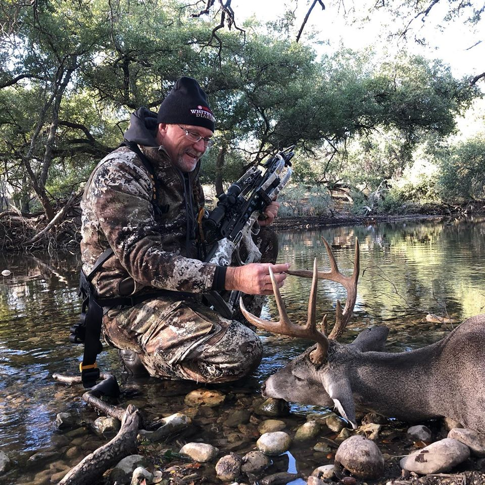 Hunter smiling with deer and crossbow