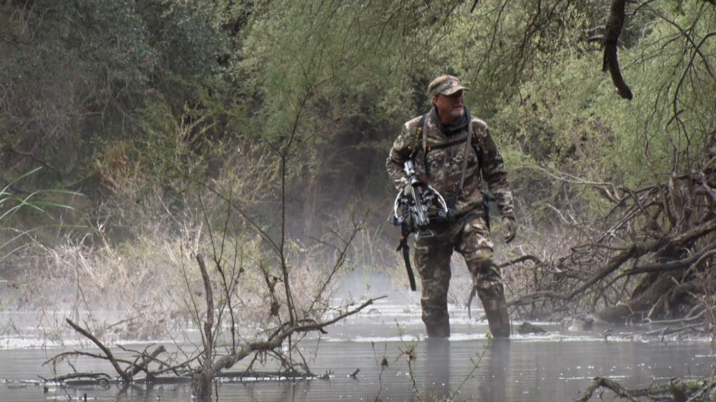 Hunter wading through water with crossbow